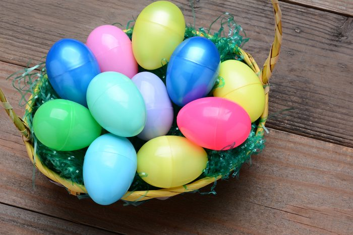High Angle view of a basket filled with colorful plastic Easter eggs. Horizontal format on a rustic wood background.