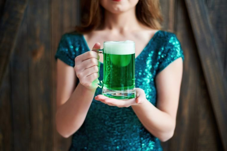 Mug of green beer for St. Patricks Day in woman hands on wooden background. Girl in emerald sequins dress holding glass of beer in pub. Greeting card, March 17