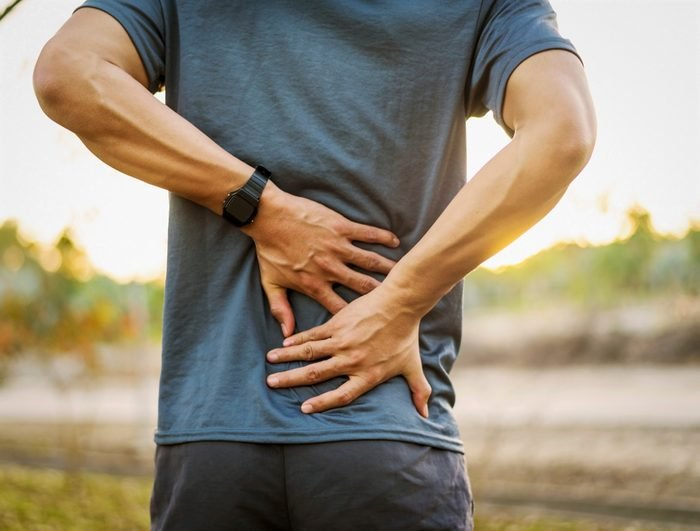 Back pain, close up young man has injury during outdoor exercise