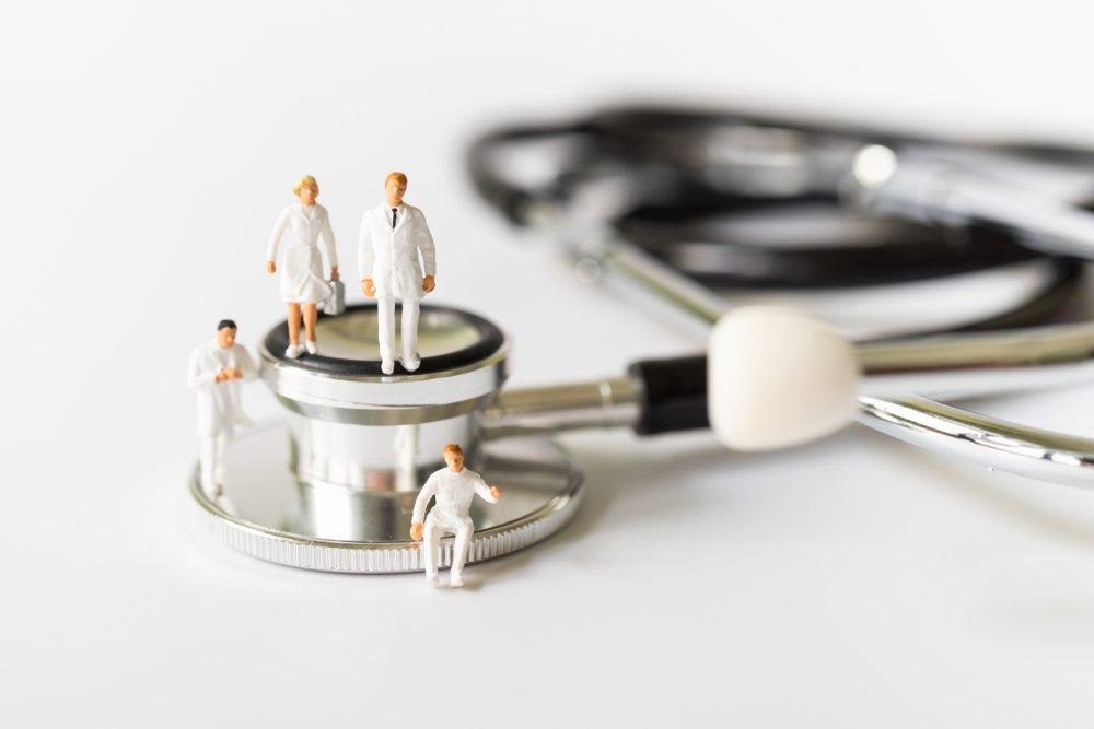 Miniature people, Doctor and Nurse emergency medical team on stethoscope on white background.