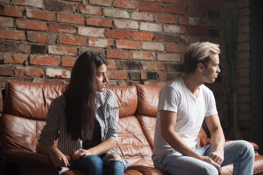 Angry frustrated husband ignoring wife, avoiding looking at her or talking after serious quarrel, sad girlfriend trying to fix relationship problem, spouses having disagreement or misunderstanding.
