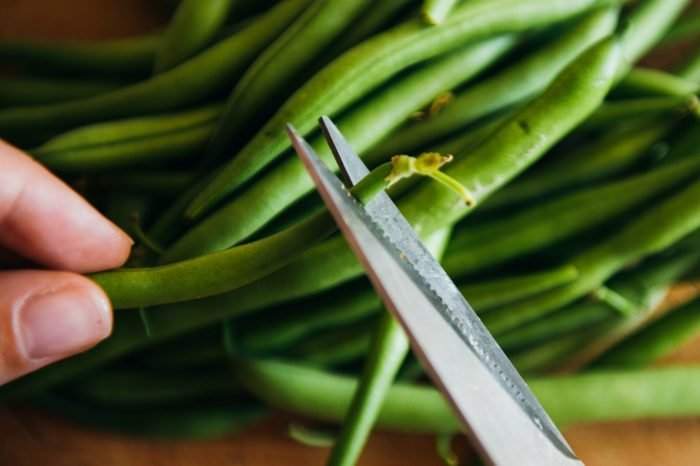 Green Beans on a grey concrete background wooden board cutting with scissors healthy food cooking