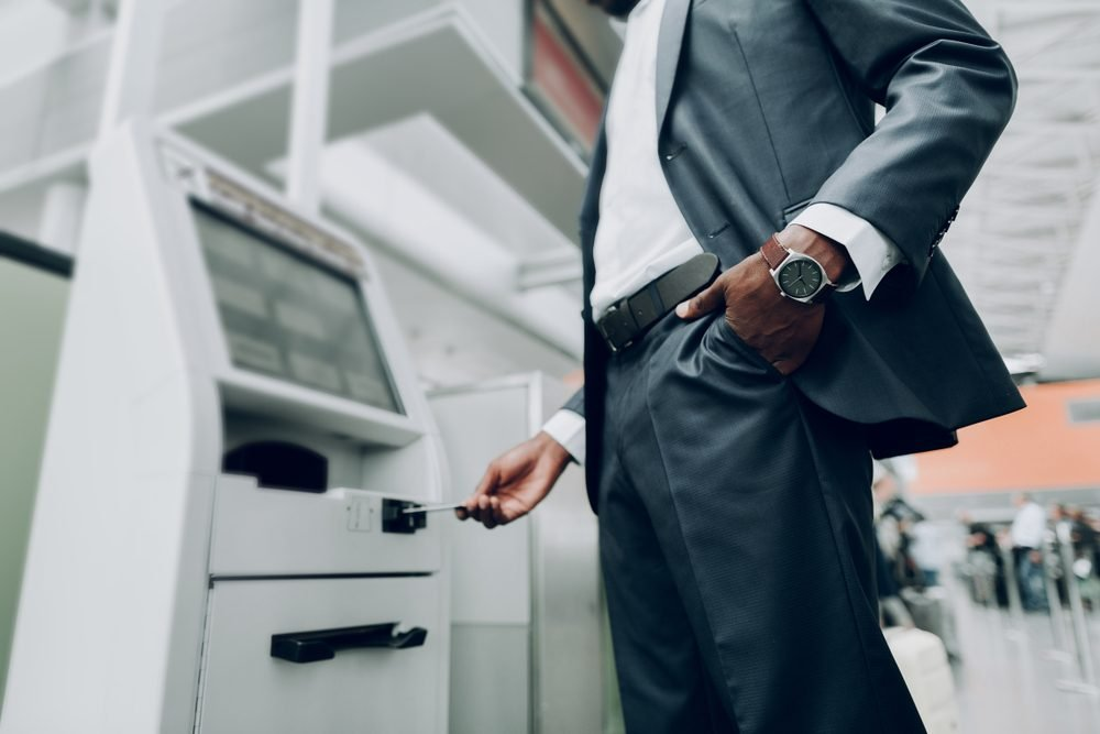 Close up of male is holding hand with watch in his pocket, while standing near cash dispenser