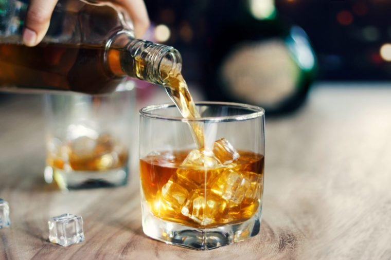 Man pouring whiskey in glasses of whisky drink alcoholic beverage with friends at bar counter in the pub.