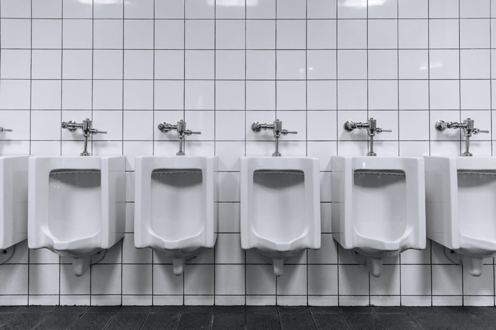Clean male toilet row of urinals in a public restroom black and white
