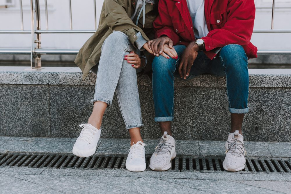 Low angle of a nice young international couple sitting in urban setting s while feeling happy together