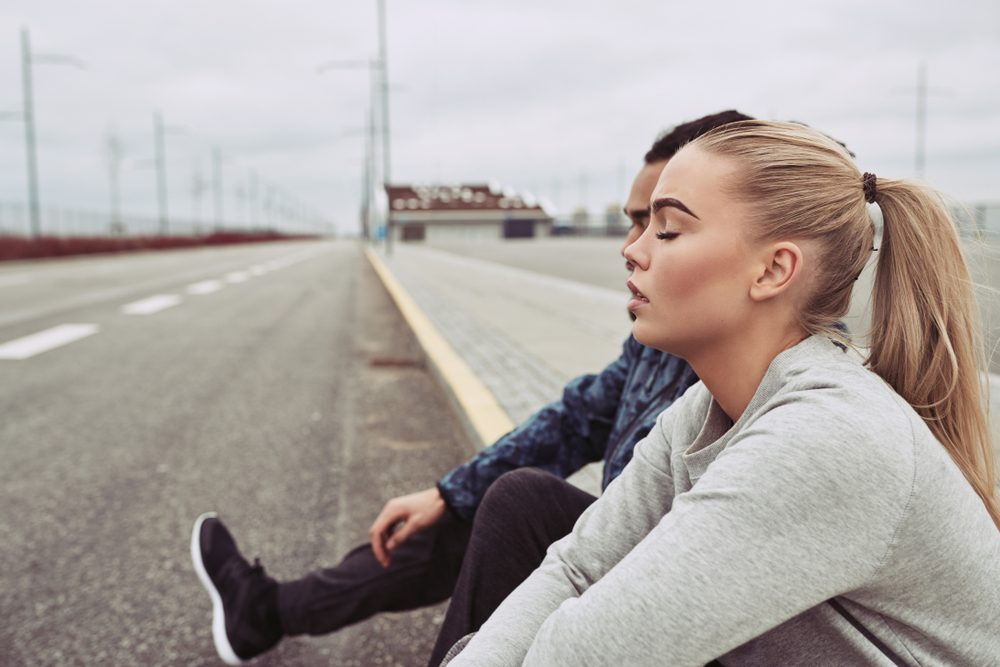 Diverse young couple in sportswear sitting on the side of a road together taking a break from a run on an overcast day