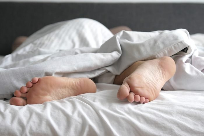 Man sleeping in bed feet relax on holidays. Close up of men feet