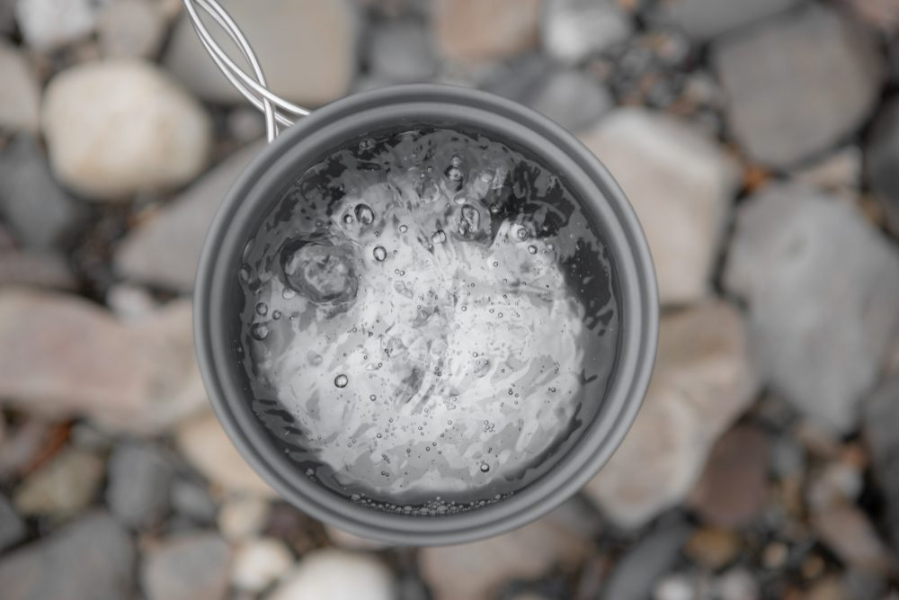 Metal Gray Mug With Boiling Water Close-Up On Background Of River Stones, Top View. Boiling Water In The Campaign.