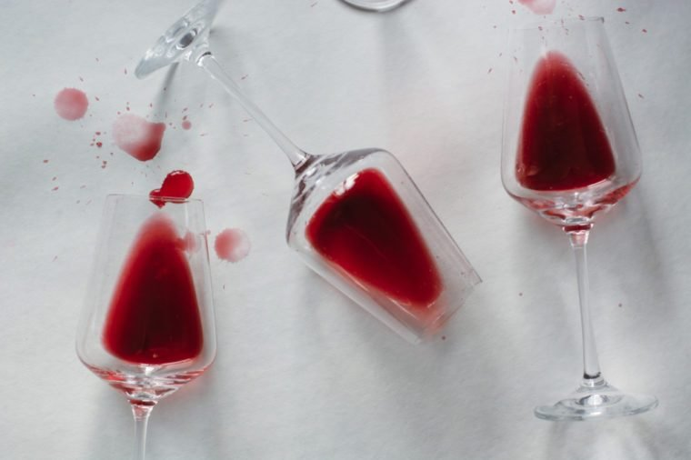 Glasses of spilled red wine on white background, copy space. Wine degustation concept