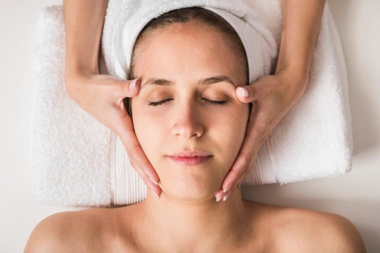 Spa concept. Face massage. Young woman getting spa treatment, close up