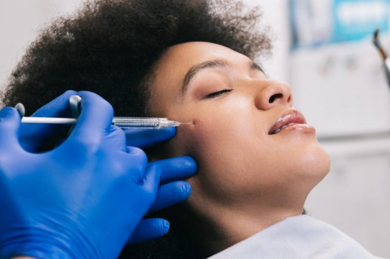 Attractive young African woman is getting a rejuvenating facial injections. She is sitting calmly at clinic. The expert beautician is filling female wrinkles by hyaluronic acid.