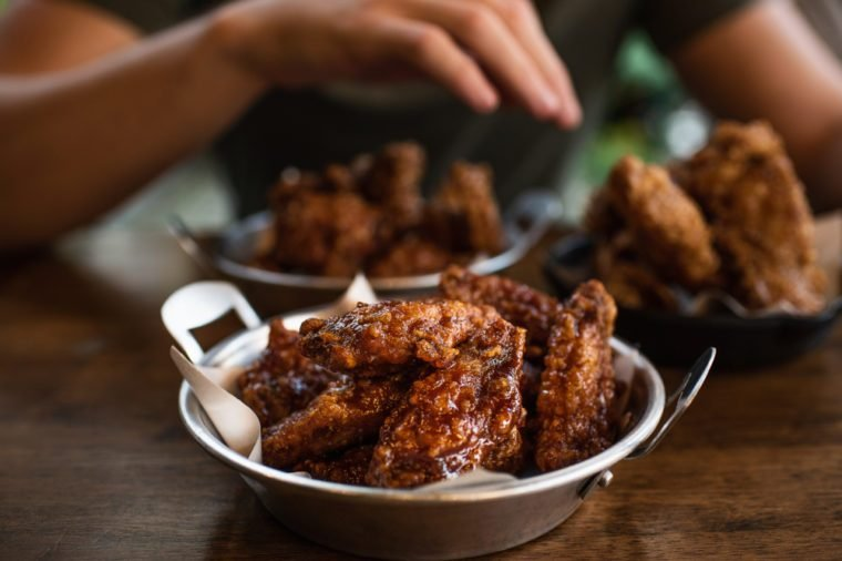 A man eating spicy sticky chicken wings with plastic gloves from a metal circular bowl