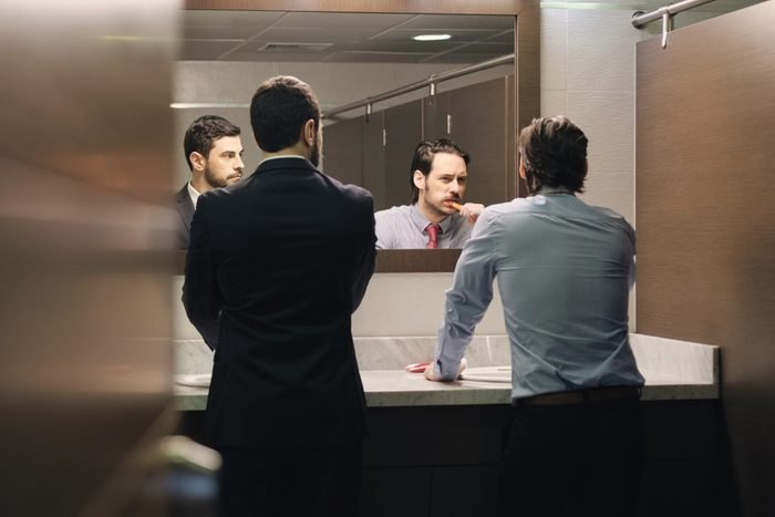 Business people in office bathroom. Young man using corporate restroom, washroom and lavatory. Public toilet in building with manager brushing teeth after lunch break