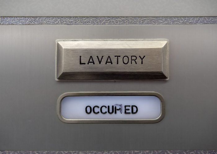 """Close up of an occupied sign on an aircraft bathroom door indicating the bathroom is in use. The word """"occupied"""" is slightly obscured by smeared ink in the middle of the word"""