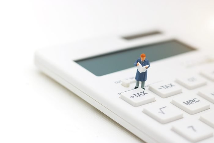 Miniature people: Businessman reading book on calculator, Education or business concept.