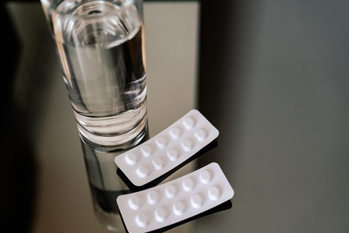 pills medicine tablets and glass of water, healthcare and medicine recovery concept