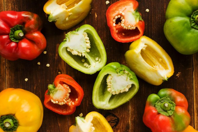 Group of colorful peppers on the wooden background. Viewed from above.