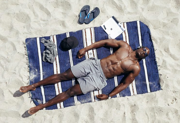 Top view of young guy lying shirtless on a mat sunbathing. African male model relaxing on beach on a hot summer day.