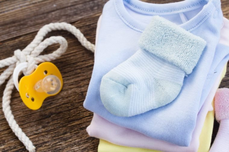 newborn baby clothes and blue socks on wooden background