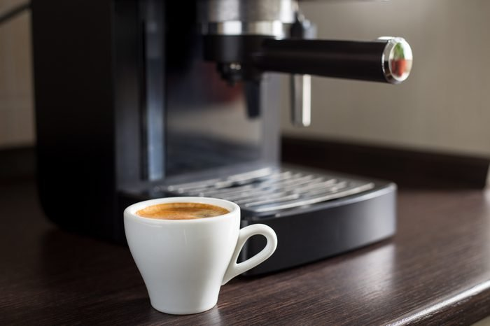 White ceramic cup of espresso with coffee ma?hine on the table. Brewing coffee at work