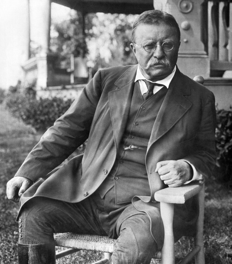 VARIOUS Cove Neck, New York: c. 1907 President Theodore Roosevelt seated in a chair outside his Sagamore Hill home on Long Island.