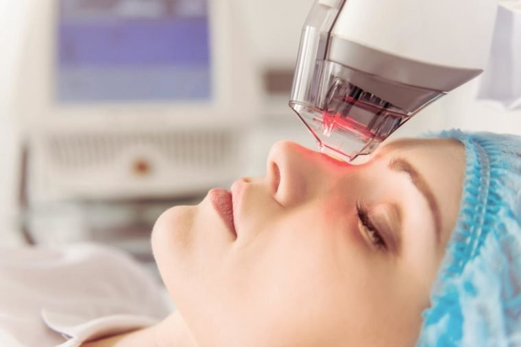 Beautiful female patient is getting a face skin treatment while lying at cosmeticians office, close up
