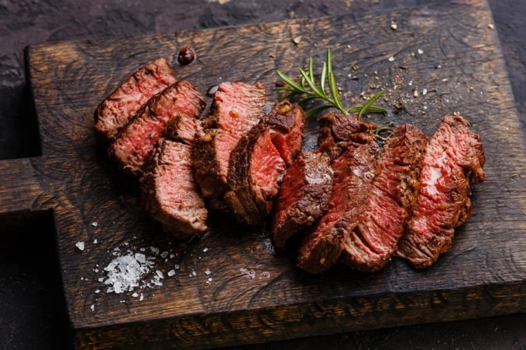 Sliced grilled steak roastbeef and rosemary on wooden cutting board background