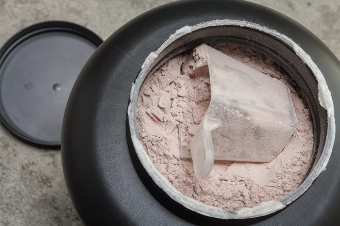 A scoop of fine Whey Protein Isolate Pure powder in a container