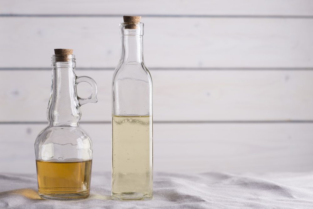 Transparent bottles with oil and vinegar on white wooden background.