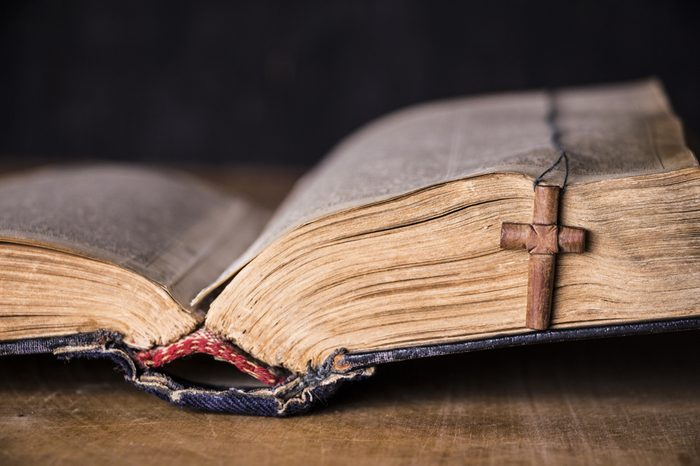 Brown cross on the Bible on a wooden background. Holy book.