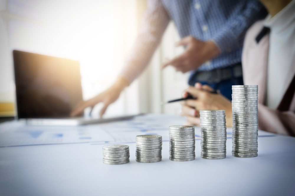 person pointing writing goals on a paper,writing business plan at workplace,man holding pens ,papers,notes in documents,Saving money concept,graph, stacks of coins ,chart and pen.