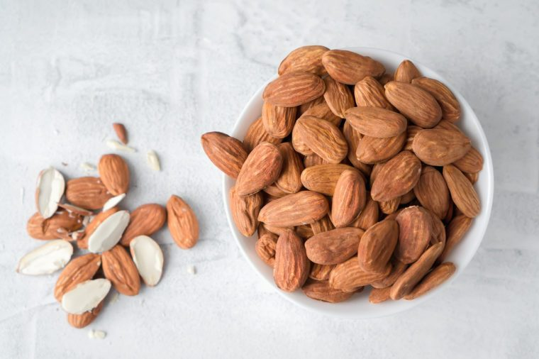 Almonds in ceramic bowl on concrete background. Top view
