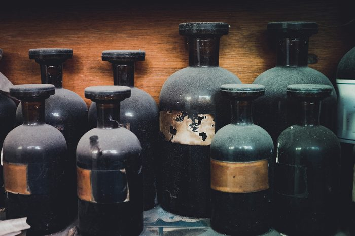 vintage closeup image of still life composition,dusty chemical bottle on wooden rack.selective focus shot