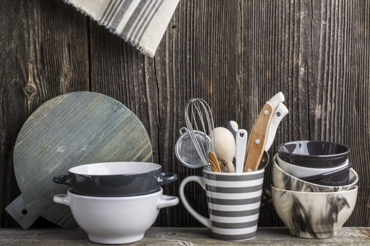 Cookware in gray and tools on a wooden kitchen shelf in the background rustic wooden wall. The horizontal design