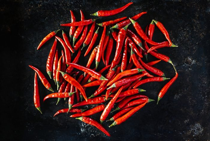 Red chili peppers on old black metal background.