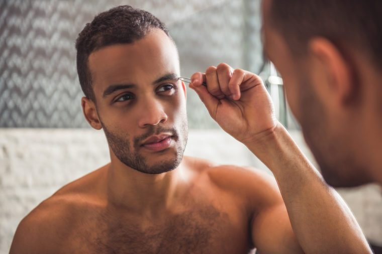 Handsome naked Afro American man is plucking eyebrows while looking into the mirror in bathroom
