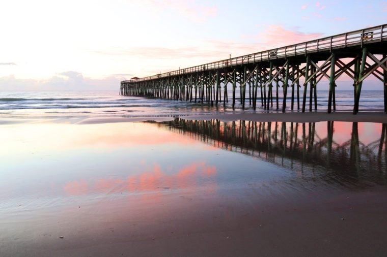 Early morning at deserted atlantic ocean beach. Marine landscape with wooden pier in South Carolina, Myrtle Beach area, USA.