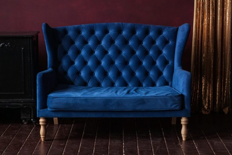 Marsala wall, golden curtain and vintage upholstered blue sofa