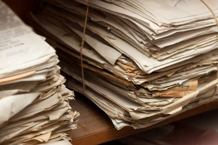 Old dusty stack of papers, files, documents on the shelves of archive room