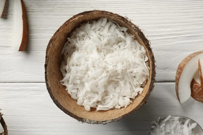 Grated coconut in shell on wooden background