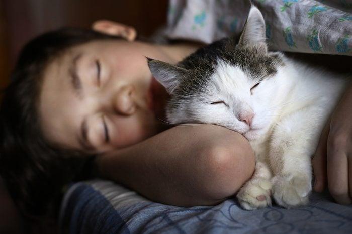 teen boy sleep with cat in bed hug close up photo