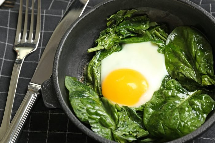 Delicious eggs Florentine in frying pan and napkin on wooden kitchen table
