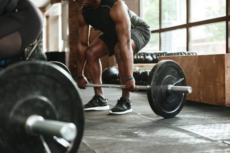 7765fb429d98 Cropped image of a young african sportsman lifting a barbell at the gym