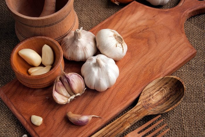 Garlic. sliced garlic, garlic clove, garlic bulb in wooden bowl place on chopping block on vintage wooden background. Place for text, copy space Concept of healthy food.