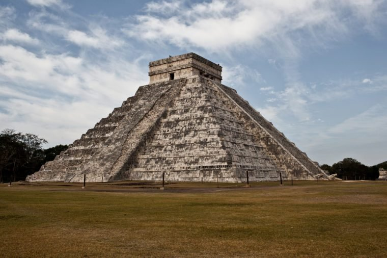 A photo of El Castillo or the Temple of Kukulcan against a blue sky with clouds at the Mayan archaeological site of Chichen Itza located on the Yucatan Peninsula in Mexico.