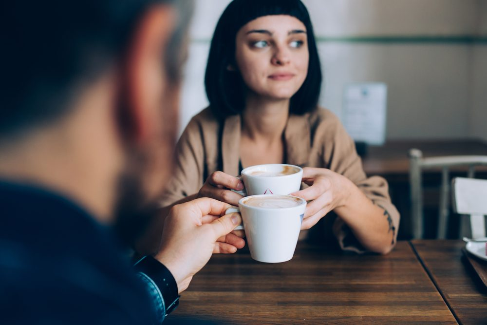 Woman and man, partners of boyfriend and girlfriend are on romantic date getaway in cute adorable cafe, they drink coffee with milk, beautiful girl looks out into window