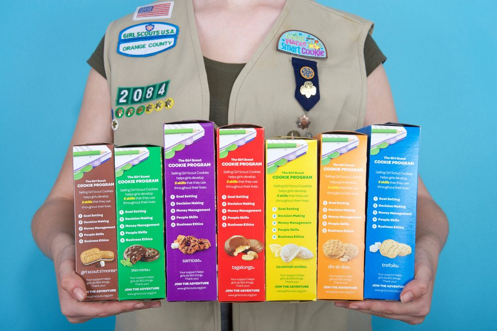 Girl scout holding cookie boxes