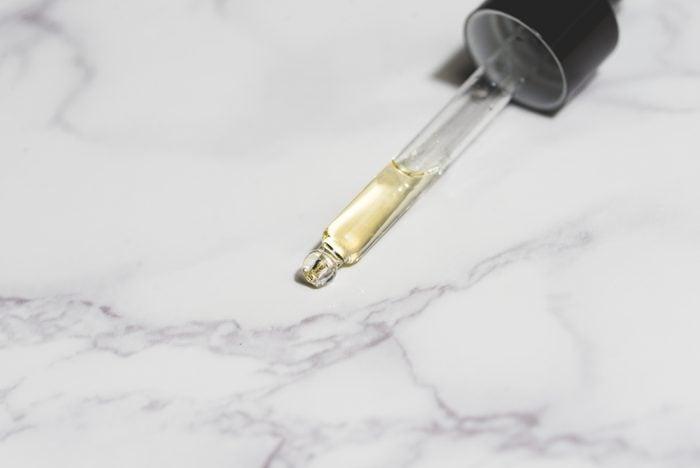 beautiful flat lay skin care yellow serum liquid oil dropper white background