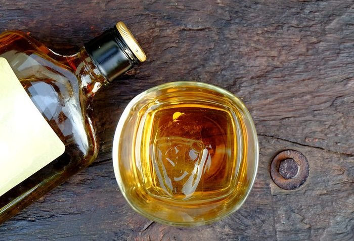 Glass with whiskey and bottle on wooden table,top view.
